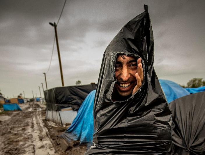 "A migrant protects himself from the rain with a plastic trash bag in the ""New Jungle"" migrant camp in Calais, where thousands of migrants live in the hope of crossing the Channel to Britain (AFP Photo/Philippe Huguen)"