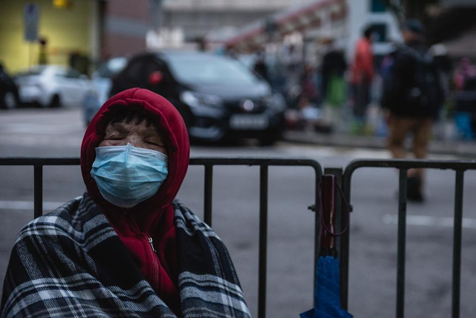 A customer sleeps while waiting for a store selling face masks to open. Thousands of Hong Kong residents waited overnight for a store selling face masks to open. Customers were only allowed to purchase two packs of masks per person. Some customers ended up waiting for over 20 hours for the store to open. (Photo by Aidan Marzo / SOPA Images/Sipa USA)