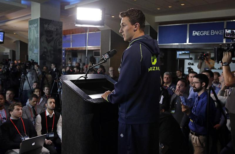 Texas A&M quarterback Johnny Manziel is surrounded by the media as answers a question during a news conference at the NFL football scouting combine in Indianapolis, Friday, Feb. 21, 2014