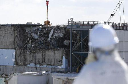 A member of the media, wearing a protective suit and a mask, looks at the No. 3 reactor building at Tokyo Electric Power Co's tsunami-crippled Fukushima Daiichi nuclear power plant in Okuma town