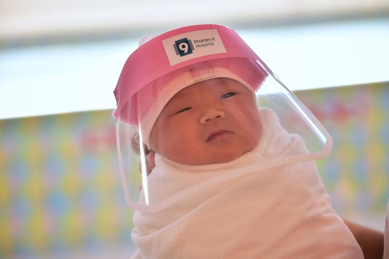 TOPSHOT - This photo taken through a glass window at a maternity ward shows a newborn baby wearing a face shield, in an effort to halt the spread of the COVID-19 coronavirus, at Praram 9 Hospital in Bangkok on April 9, 2020. (Photo by Lillian SUWANRUMPHA / AFP) (Photo by LILLIAN SUWANRUMPHA/AFP via Getty Images)