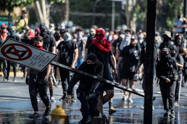 Demonstrators clash with riot police during a protest in Santiago, on October 21, 2019 (AFP Photo/Pedro UGARTE)
