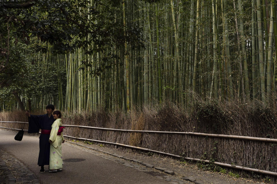 A couple takes a selfie at the Arashiyama Bamboo Forest in Kyoto, Japan, March 18, 2020. Widening travel restrictions and closures of most tourism and entertainment venues have gutted the tourism industry in many parts of the world, as well as in Japan.(AP Photo/Jae C. Hong)