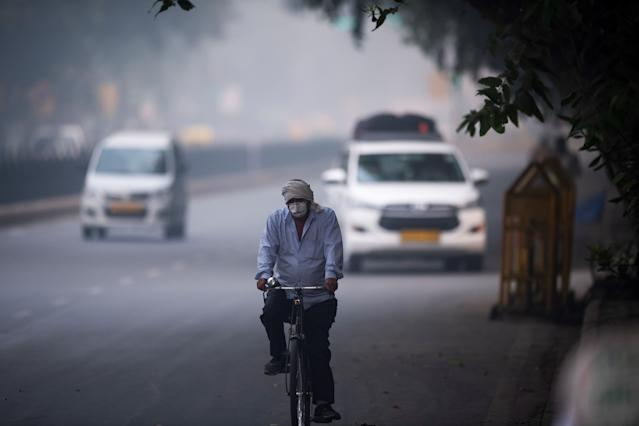A man wearing protective face mask rides a bicycle along a street in smoggy conditions in New Delhi on Nov. 1, 2019. (Photo: Jewel Samad/AFP via Getty Images)