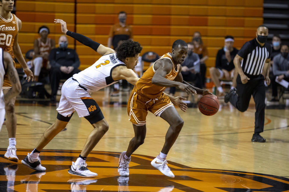 Oklahoma State guard Cade Cunningham (2) reaches for the ball as Texas guard Andrew Jones (1) dribbles down the court during the first half of the NCAA college basketball game in Stillwater, Okla., Saturday, Feb. 6, 2021. (AP Photo/Mitch Alcala)