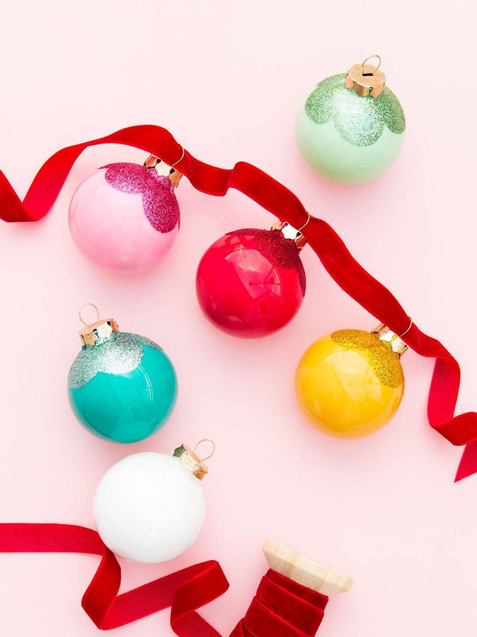 """<p>Short on time? While the scalloped glitter embellishment looks extra sweet, you could still create a very pretty Christmas garland with just colored ornaments and velvet ribbon. </p><p><a href=""""https://sarahhearts.com/diy-glitter-scallop-ornaments/"""" rel=""""nofollow noopener"""" target=""""_blank"""" data-ylk=""""slk:Get the tutorial."""" class=""""link rapid-noclick-resp"""">Get the tutorial.</a></p><p><a class=""""link rapid-noclick-resp"""" href=""""https://www.amazon.com/Darice-2-Piece-Glass-Balls-2610-48/dp/B002Z1WG0O?tag=syn-yahoo-20&ascsubtag=%5Bartid%7C10072.g.37499128%5Bsrc%7Cyahoo-us"""" rel=""""nofollow noopener"""" target=""""_blank"""" data-ylk=""""slk:SHOP ORNAMENTS"""">SHOP ORNAMENTS</a><br></p>"""