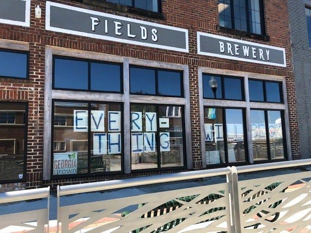 """Letters reading """"Every-thing will be OK"""" hang from a shuttered brewery in downtown Albany."""