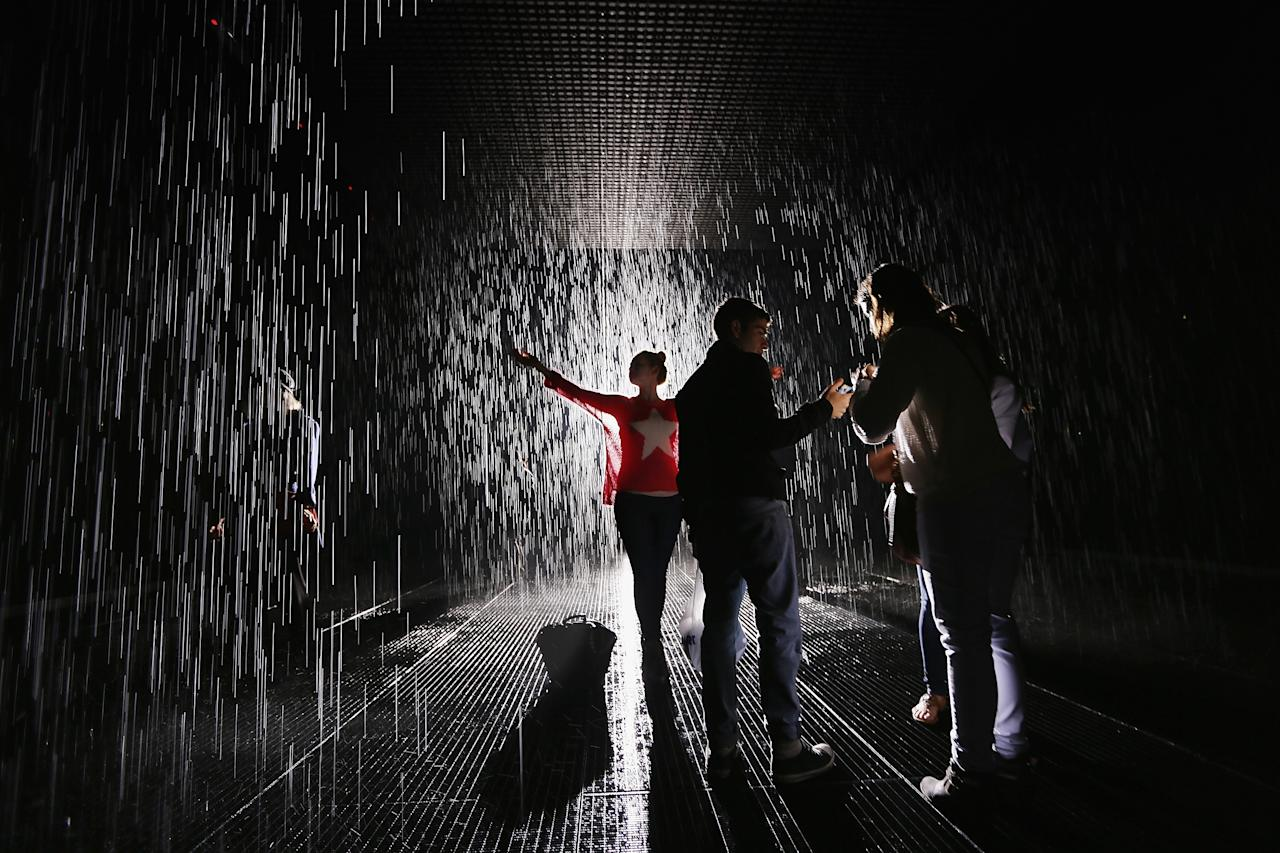 NEW YORK, NY - MAY 15:  Visitors gather in the new 'Rain Room' installation at the Museum of Modern Art (MoMA) in Manhattan on May 15, 2013 in New York City. The 5,000 square-foot installation creates a field of falling water that stops in the area where people walk through, allowing them to remain dry. The piece, created by Random International, releases a 260-gallon per minute shower around visitors.  (Photo by Mario Tama/Getty Images)