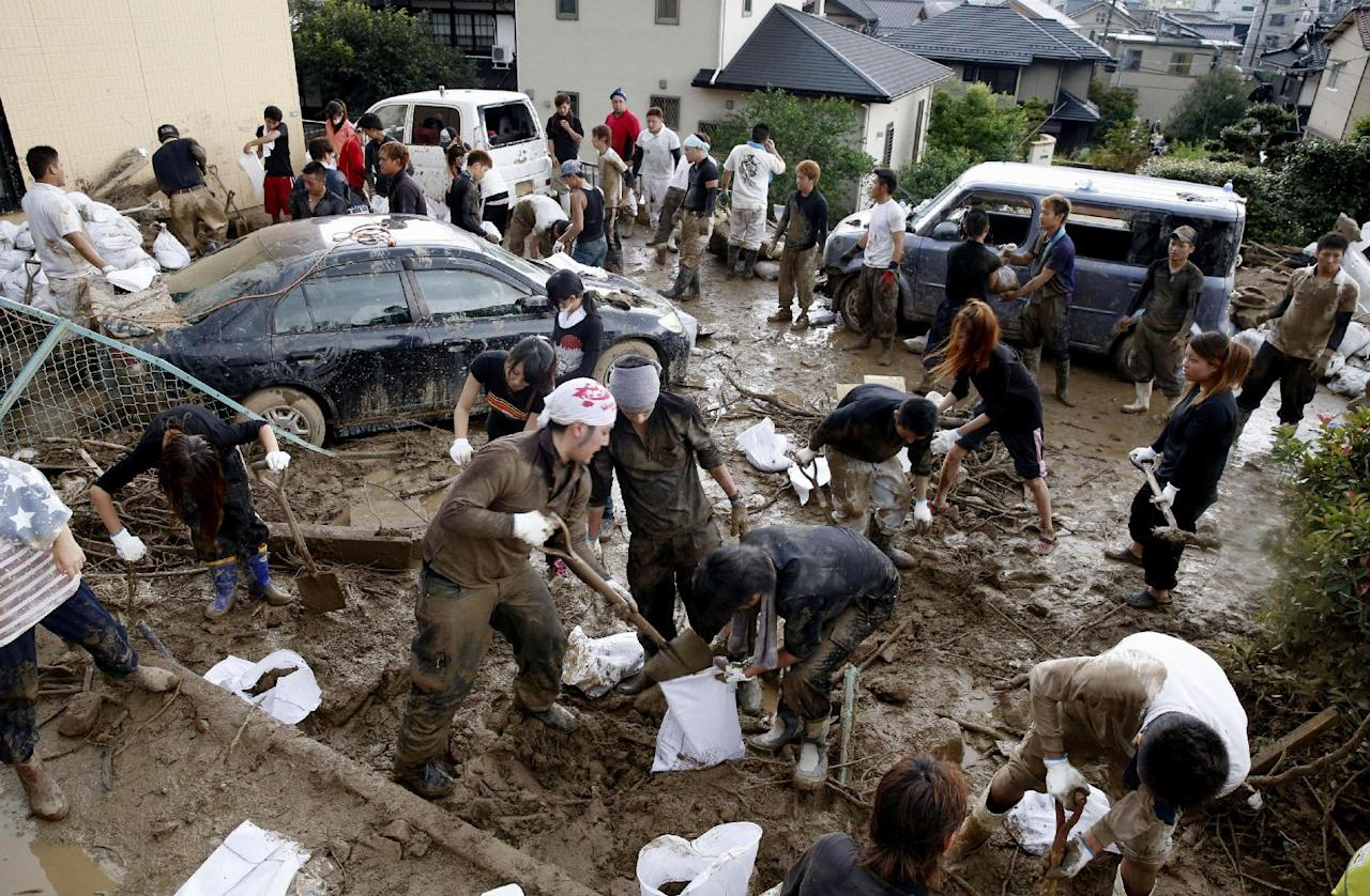 People remove the mud and the rubble in a mud-covered residential area following a massive landslide in Hiroshima, western Japan, Sunday, Aug. 24, 2014. Dozens of people were dead after torrents of mud, rocks and timber swept through at least five valleys in Hiroshima's suburbs after heavy rains early Wednesday. About 2,800 police and military personnel have been searching for the victims, at times suspending their work to reduce risks from further slides. (AP Photo/Kyodo News) JAPAN OUT