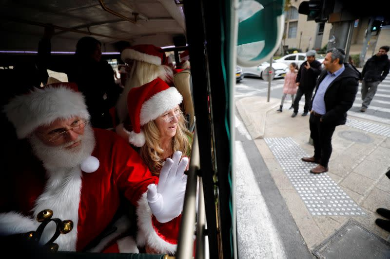 People dressed in Santa Claus outfits wave from inside a bus as they make their way to visit Jerusalem's Old City as a group of Santa Clauses from around the world, in Jerusalem
