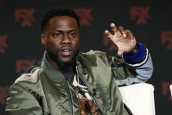 Kevin Hart in an olive-drab jacket raising his hand