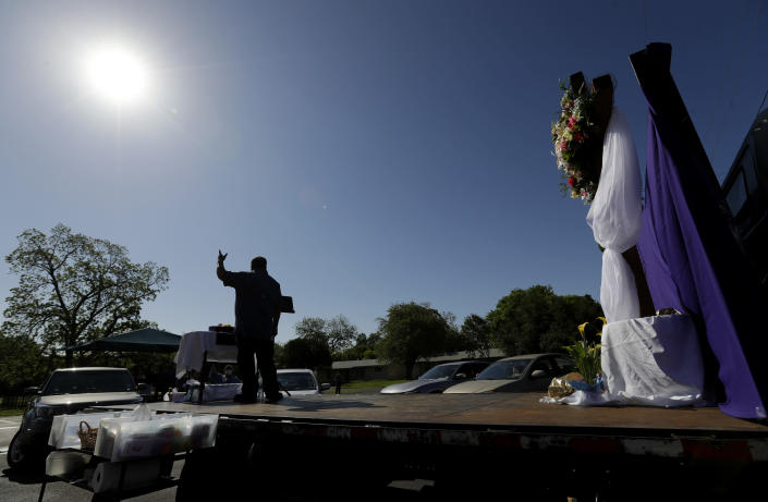 "Pastor Albert ""Gonzo"" Gonzales stands on a flat-bed truck as his church holds Easter services in the parking log in San Antonio, Sunday, April 12, 2020. Many churches are adapting their services as Christians around the world are celebrating Easter at a distance due to the COVID-19 pandemic. (AP Photo/Eric Gay)"