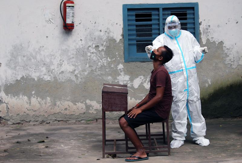 A health worker in personal protective equipment collects a swab sample from a patient for Covid-19 in New Delhi. Source: Getty