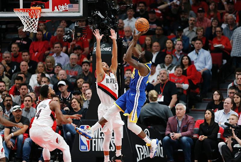 Golden State's Draymond Green shoots the ball against Portland's CJ McCollum on the way to a triple-double in the Warriors' overtime victory over the Trail Blazers in game four of the NBA Western Conference finals (AFP Photo/JONATHAN FERREY)