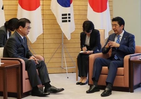 Japan's Prime Minister Shinzo Abe talks with South Korea's National Intelligence Service chief Suh Hoon during their meeting in Tokyo