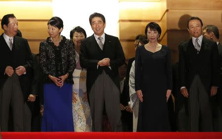 Japan's Prime Minister Shinzo Abe (front C) exchanges smiles with his cabinet ministers, including Economy, Trade and Industry Minister Yuko Obuchi (front 2nd L), Internal Affairs and Communications Minister Sanae Takaichi (front 2nd R), Deputy Prime Minister and Finance Minister Taro Aso (R) and others as they prepare for a photo session at his official residence in Tokyo September 3, 2014. REUTERS/Toru Hanai