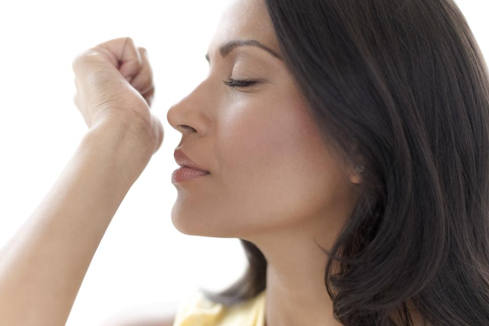 Woman smelling perfume on her wrist.
