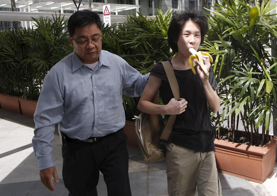 Amos Yee eats a banana as he arrives with his father to the State Courts for a pre-trial conference in Singapore April 17, 2015. The Singaporean has been charged with harassment and insulting a religious group for comments he made on social media about former premier Lee Kuan Yew and Christians soon after Lee's death, authorities said on March 31, 2015. REUTERS/Edgar Su
