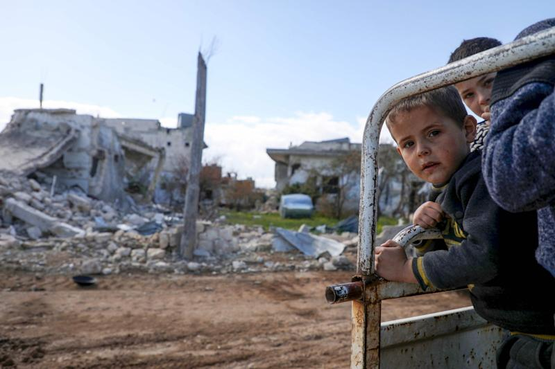 Displaced Syrian boys look towards the camera from the back of their family truck as they visit their home in the village of al-Nayrab, northwest Syria: AFP via Getty Images