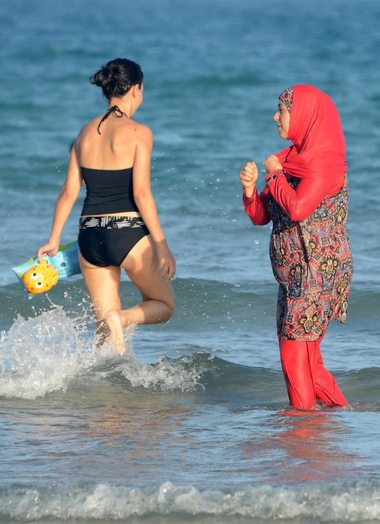 """Tunisian women, one (R) wearing a """"burkini"""", a full-body swimsuit designed for Muslim women, pictured at Ghar El Melh beach near Bizerte, northeast of the capital Tunis, on August 16, 2016 (AFP Photo/Fethi Belaid)"""