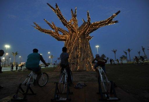 South Africans light up a Baobab tree by riding bikes in Durban in 2011 as part of a renewable energies display on the beach front during the UN Climate Change Conference (COP17). Climate change caused by global warming is freezing the world economy, a report commissioned by 20 of the world's most vulnerable countries said Wednesday