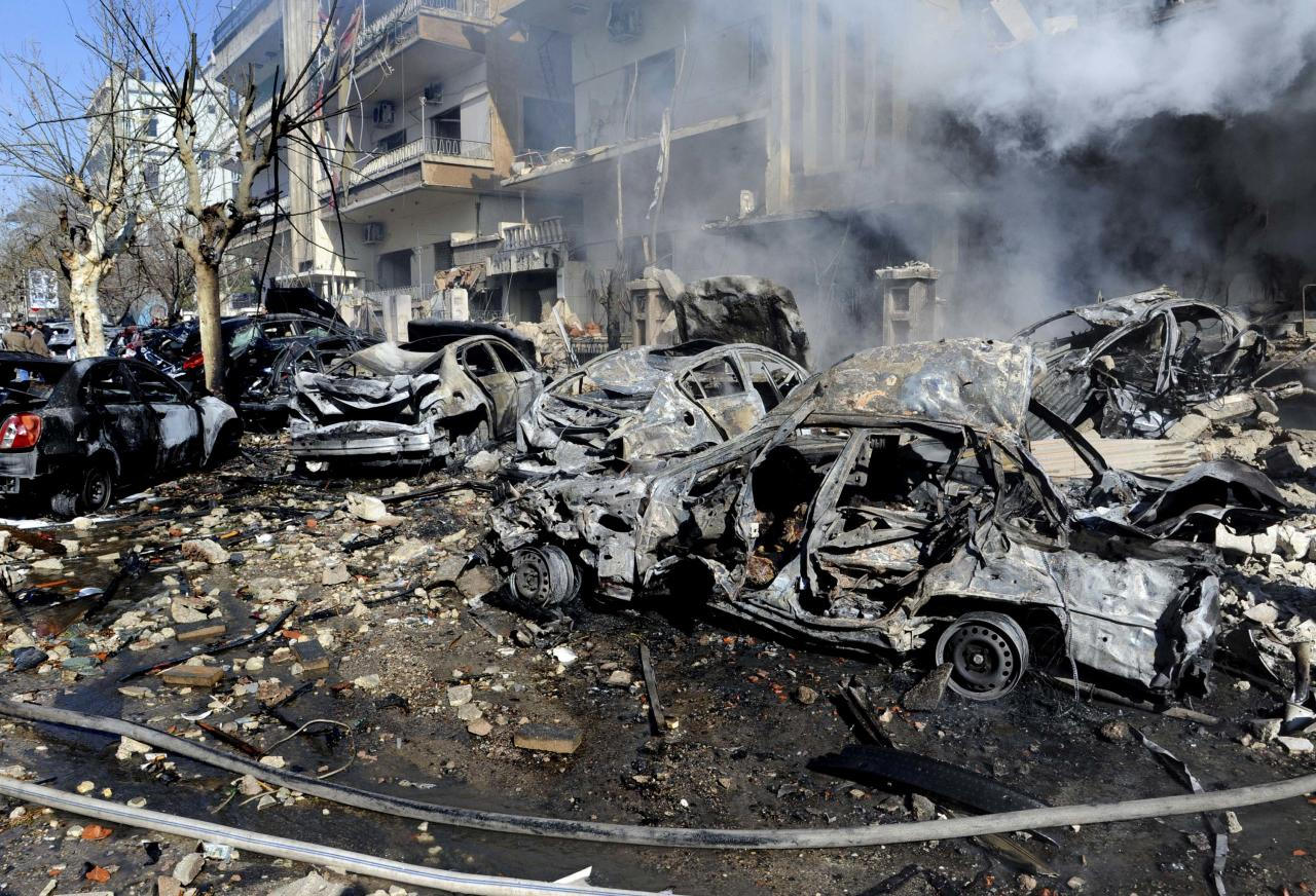 In this photo released by the Syrian official news agency SANA, burnt and destroyed cars are seen near the aviation intelligence department, which was attacked by one of two explosions, in Damascus, Syria, on Saturday, March 17, 2012. Twin bombings struck government targets in the Syrian capital early Saturday, killing security forces and civilians and leaving pools of blood and carnage in the streets, according to state-run television. (AP Photo/SANA)