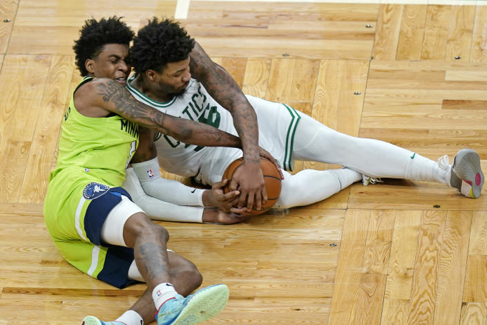 Minnesota Timberwolves forward Jaden McDaniels, left, and Boston Celtics guard Marcus Smart (36) compete for the ball on the floor in the second half of an NBA basketball game, Friday, April 9, 2021, in Boston. (AP Photo/Elise Amendola)