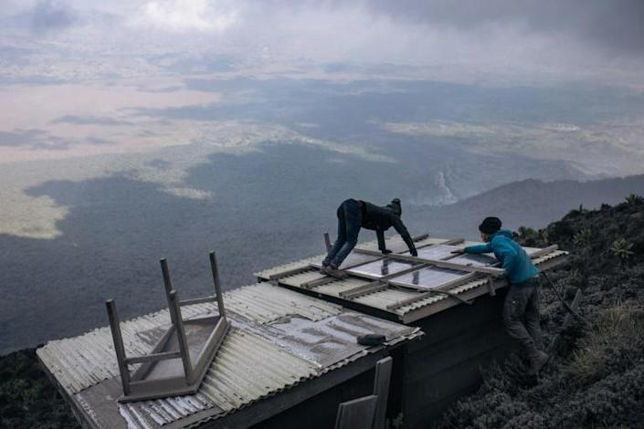 Volcanologists clean solar panels that help to power their monitoring station on Nyiragongo