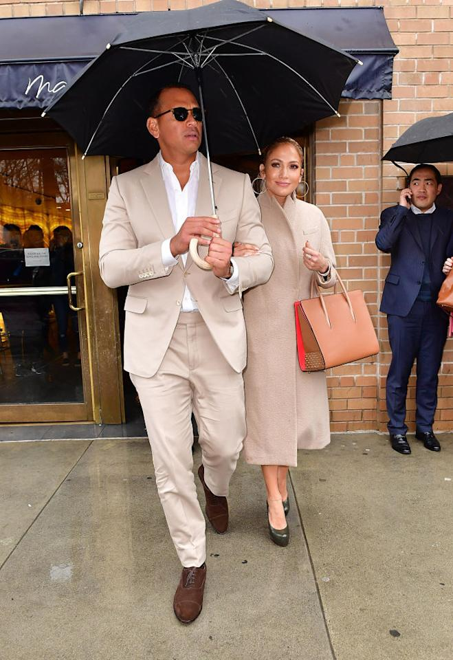 <p>New couple Jennifer Lopez and Alex Rodriguez stepped out together in matching beige ensembles on March 31 in New York City. Lopez donned a Max Mara coat that she paired with a Christian Louboutin studded tote, while Rodriguez sported a cream suit. (Photo: Getty Images) </p>