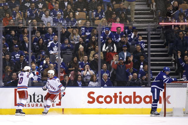 New York Rangers defenseman Tony DeAngelo (77) celebrates his goal with teammate Artemi Panarin (10) as Toronto Maple Leafs right wing Mitchell Marner (16) stands at the net during overtime NHL hockey game action in Toronto, Saturday, Dec. 28, 2019. (Cole Burston/The Canadian Press via AP)