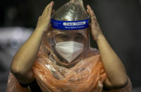A Chinese tourist in from Shanghai, who arrived at Suvarnabhumi airport on a special tourist visa, adjusts her face shield, in Bangkok, Thailand, Tuesday, Oct. 20, 2020. Thailand on Tuesday took a modest step toward reviving its coronavirus-battered tourist industry by welcoming 39 visitors who flew in from Shanghai, the first such arrival since normal traveler arrivals were banned almost seven months ago. (AP Photo/Wason Wanichakorn)