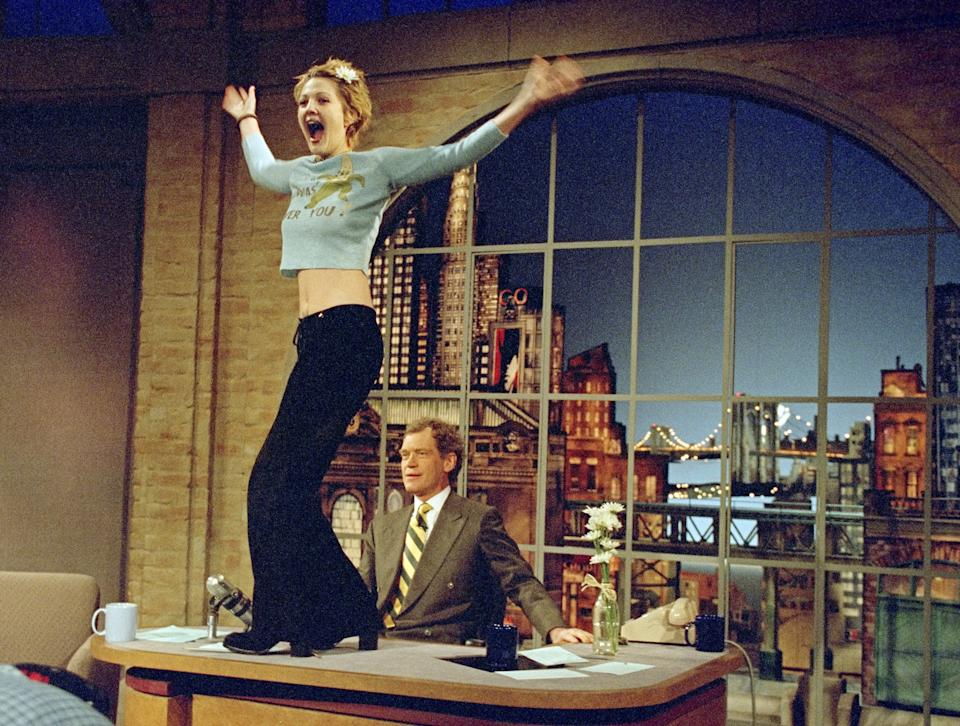 NEW YORK - APRIL 12: Drew Barrymore turns to the audience after flashing host David Letterman during the April 12, 1995 taping of the Late Show with David Letterman in New York City. This show was taped on Dave's Birthday. This photo is provided by CBS from the Late Show with David Letterman photo archive. (Photo by Alan Singer/CBS via Getty Images)