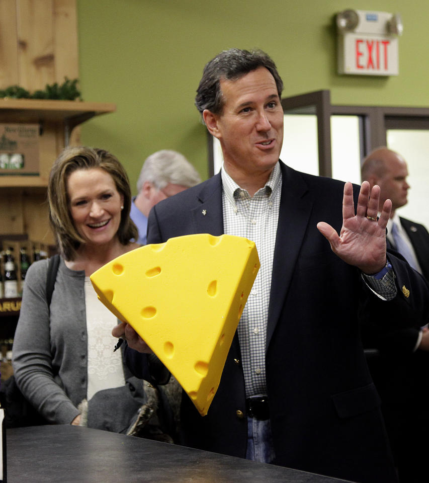 Republican presidential candidate, former Pennsylvania Sen. Rick Santorum, accompanied by his wife Karen, holds a cheese head hat at Simon's Specialty Cheese in Appleton, Wis., Monday, April 2, 2012. (AP Photo/Jae C. Hong)
