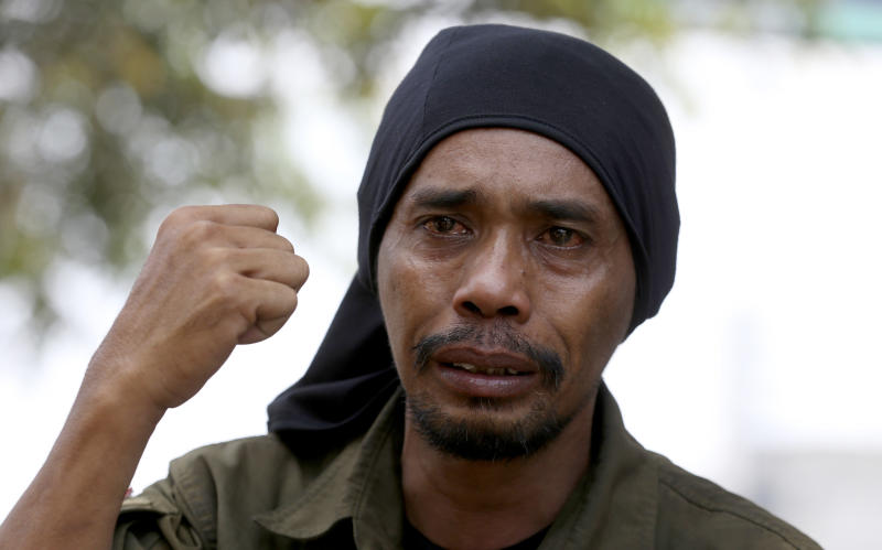 Medi Bastoni, 43, gestures as he talk to journalist in Bekasi, outskirt of Jakarta, Indonesia, Thursday, Aug, 22, 2019. The Indonesian man is walking over 700-kilometer (430-mile) backward from his home in eastern Java to the country's capital to draw awareness of deforestation.(AP Photo/Achmad Ibrahim)