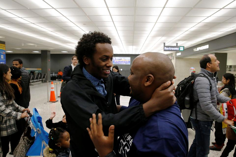 Mustafa Aidid, right, a Somali national who was delayed entry into the U.S. because of the Jan. 27 travel ban, is reunited with his brother Taha Aidid, left, at Washington Dulles International Airport in Chantilly, Virginia on Feb. 6, 2017.