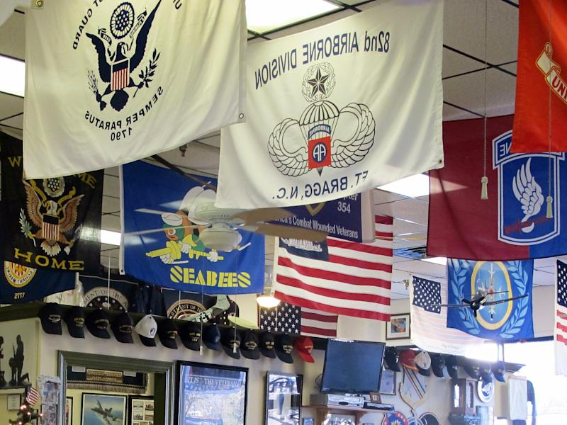 This Dec. 17, 2013, photo shows flags hanging from the ceiling of the Veterans Cafe in Myrtle Beach, S.C. In the four years the cafe has been open it has become a combination of an eatery, a military museum and place to hang out for those who served the nation in the military. (AP Photo/Bruce Smith)