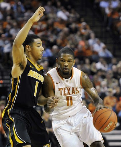 Texas guard Julien Lewis (0) drives past Missouri guard Phil Pressey (1) during the first half of an NCAA college basketball game, Monday, Jan. 30, 2012, in Austin, Texas. (AP Photo/Michael Thomas)