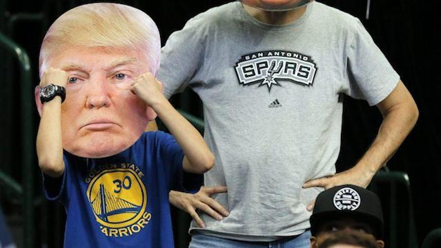 "A <a class=""link rapid-noclick-resp"" href=""/nba/players/4612/"" data-ylk=""slk:Stephen Curry"">Stephen Curry</a> T-shirt-wearing NBA fan sported a Donald Trump mask at a game earlier this season. (AP)"