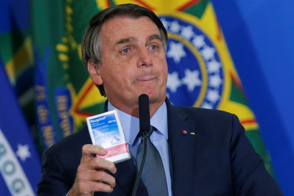 Brazil's President Jair Bolsonaro holds a box of chloroquine during an inauguration ceremony of the new Health Minister Eduardo Pazuello (not pictured) at the Planalto Palace in Brasilia, Brazil, September 16, 2020. REUTERS/Adriano Machado