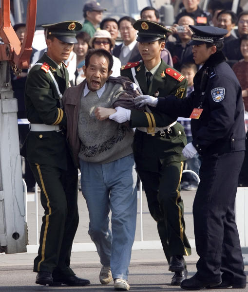 "FILE - In this Oct. 21, 2007 file photo, a Chinese protester shouting ""Down with corruption"" is hauled away near the Great Hall of the People where the 17th Chinese Communist Party Congress is held in Beijing, China. Chinese authorities have shut down or frozen the microblog accounts of several prominent liberal intellectuals and harassed rights lawyers lobbying against unofficial ""black jails,"" underlining the determination of the country's new leadership to control dissent even as it vows to root out corruption. (AP Photo/Ng Han Guan, File)"