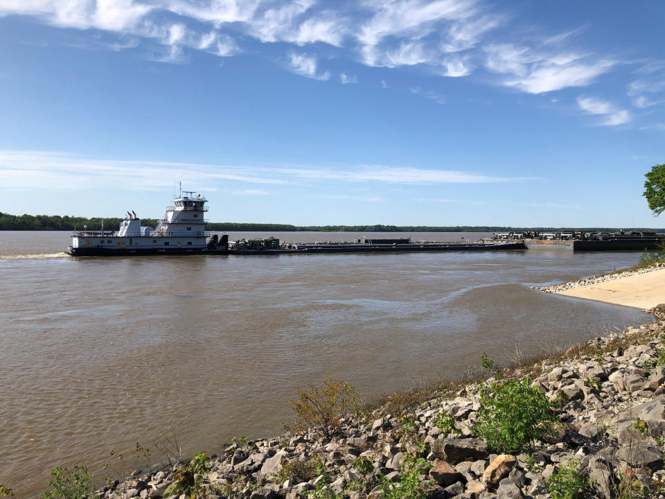 A tugboat with a barge attached sits near a boat ramp at Meeman-Shelby Forest State Park, Wednesday, May 12, 2021, in Millington, Tenn. A crack in the Interstate 40 bridge linking Tennessee and Arkansas has shut down Mississippi River traffic near Memphis, forcing tugs that are hauling barges to wait until they receive clearance that it's safe to pass under the closed bridge. (AP Photo/Adrian Sainz)