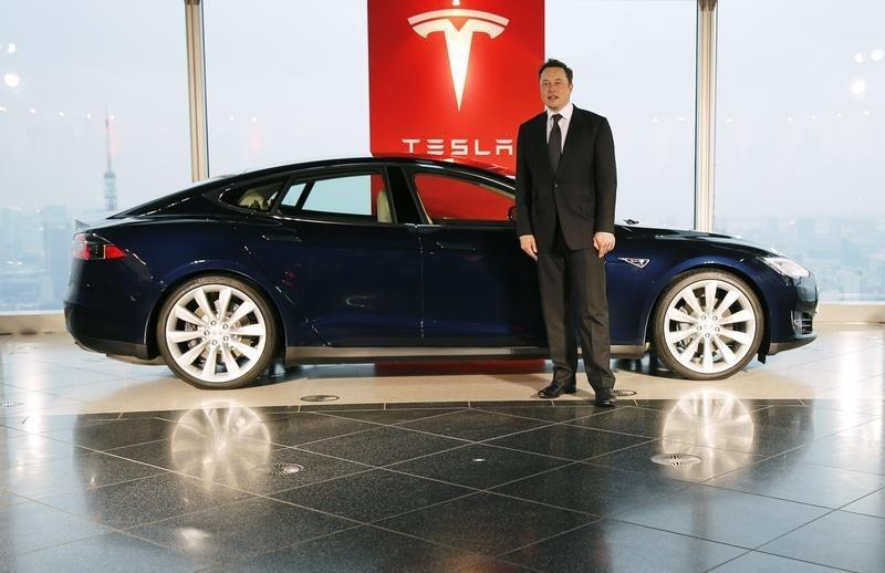 Tesla Motors Inc Chief Executive Musk poses with a Tesla Model S electric car in Tokyo