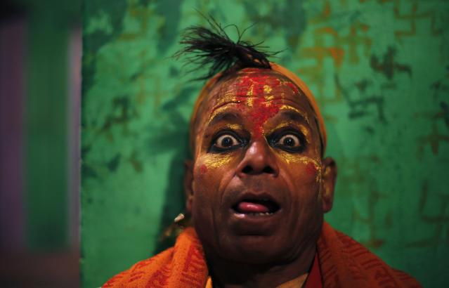 A Hindu holy man or Sadhu reacts as he waits for Hindu priest Babulal to exit a temple and walk through a bonfire, signifying the burning of the demon Holika, during a ritual to mark the first day of the Holi spring festival, also known as the Festival of Colours, at Phalen village near the northern Indian city of Mathura March 17, 2014. Holi in Phalen starts on the first day of the full moon where a Hindu mythological story will be re-enacted to symbolize the victory of good over evil, according to local media. REUTERS/Adnan Abidi (INDIA - Tags: SOCIETY RELIGION)