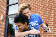 """In this Saturday, May 29, 2021, photo, provided by Gregg Gelmis, Kelly Moïse hugs her son Kieran after cutting the last braid from his hair during a live donation fundraiser, """"Kieran's Curls for Cancer,"""" for the nonprofit Children with Hair Loss in Huntsville, Ala. So far, they've raised $35,000. (Courtesy of Gregg Gelmis via AP)"""