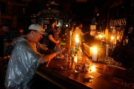 People sit at a bar that has no power and drink during a
