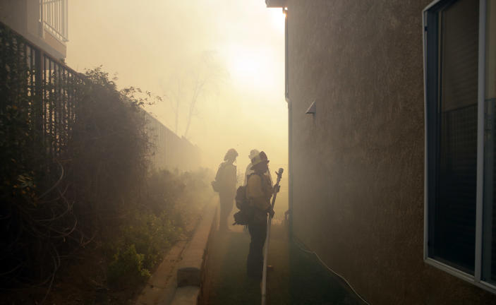 Firefighters are obscured by smoke from an advancing wildfire Friday, Oct. 11, 2019, in Porter Ranch, Calif. (AP Photo/Marcio Jose Sanchez)