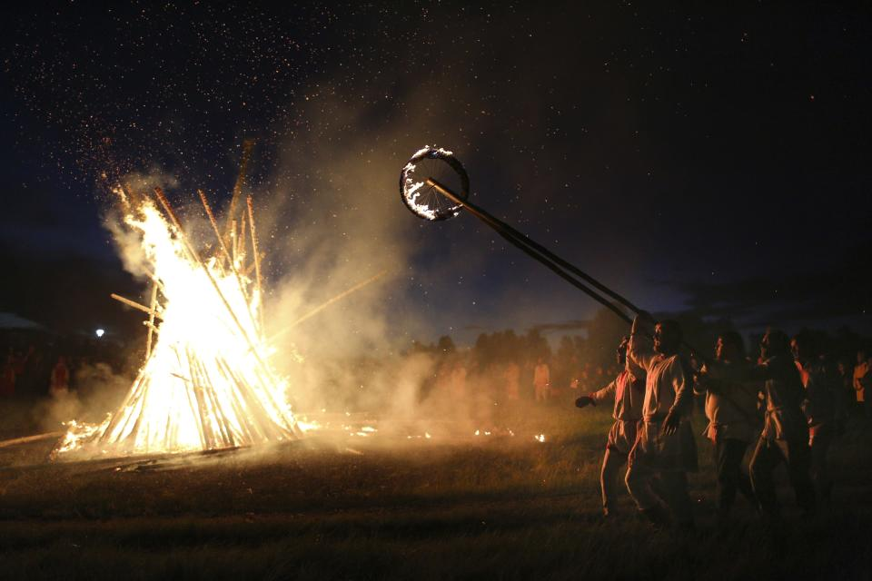 People walk around a bonfire celebrating the summer solstice in Okunevo village, some 200 kilometers (124 miles) northeast of the Siberian city of Omsk, Russia, Monday, June 21, 2021. The festivities of Ivan Kupala, or John the Baptist, are similar to Mardi Gras and reflect pre-Christian Slavic traditions and practices. (AP Photo/Evgeniy Sofiychuk)