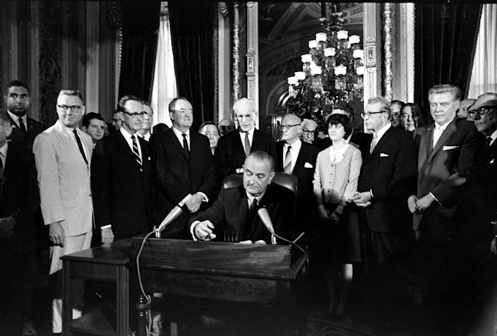 U.S. President Lyndon B. Johnson signs the Voting Rights Act of 1965 in a ceremony in the President's Room near the Senate chambers in Washington, D.C., Aug. 6, 1965. Surrounding the president from left directly above his right hand, Vice President Hubert Humphrey; Speaker John McCormack; Rep. Emanuel Celler, D-N.Y.; first daughter Luci Johnson; and Sen. Everett Dirkson, R-Ill. Behind Humphrey is House Majority Leader Carl Albert of Oklahoma; and behind Celler is Sen. Carl Hayden, D-Ariz.