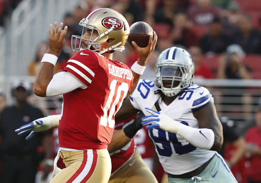 FILE - In this Thursday, Aug. 9, 2018 file photo,San Francisco 49ers quarterback Jimmy Garoppolo, left, passes in front of Dallas Cowboys defensive end Demarcus Lawrence (90) during the first half of an NFL preseason football game in Santa Clara, Calif. DeMarcus Lawrence, who finished tied for second in the NFL with 14 sacks last season and ended up with the $17.1 million franchise tag, has a sack in each of the first two games. Three fellow defensive linemen had a sack apiece against the Giants. (AP Photo/Tony Avelar, File)