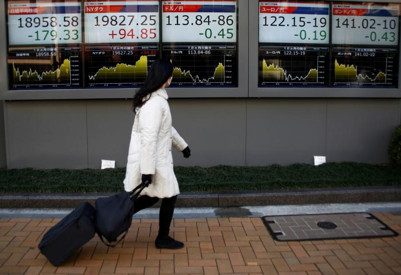 A woman walks past electronic board showing stock prices and Japanese Yen's exchange rate outside a brokerage at a business district in Tokyo